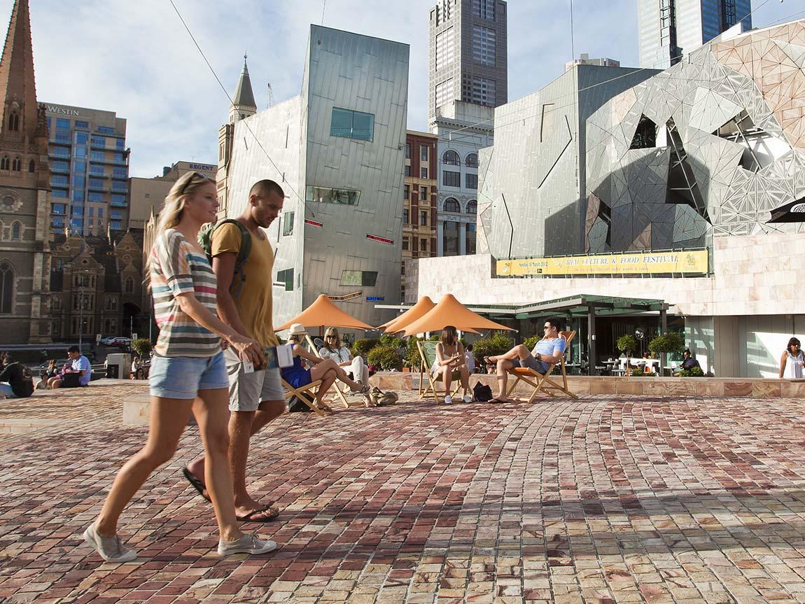 Couple walking through Federation Square, Melbourne, Victoria, Australia